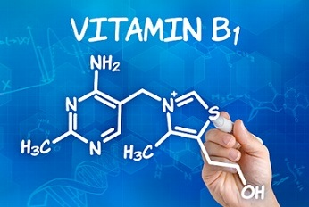 Hand with pen drawing the chemical formula of  Vitamin B1